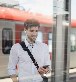 Man by Train on Phone